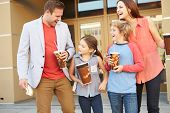 stock photo of pre-adolescent child  - Family Standing Outside Cinema Together - JPG