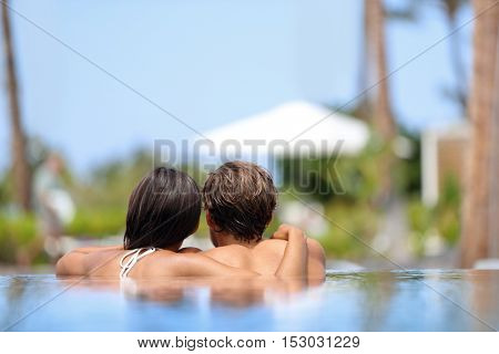 poster of Honeymoon couple relaxing together in an infinity swimming pool in luxury resort spa retreat beach d