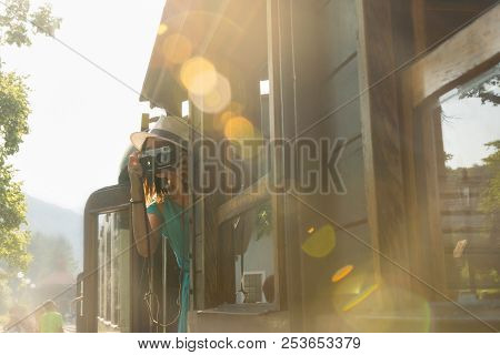 poster of Traveler Girl Taking Photo From The Train. Traveler Girl Using Old Fashioned Camera. Girl Traveler T