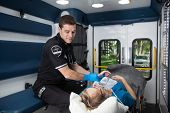 image of triage  - Male EMT professional taking pulse of a senior woman inside ambulance - JPG