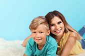 Mother And Son Lying On Fuzzy Rug Near Color Wall poster