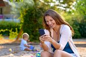 Vivacious Young Mother Laughing At A Text Message On Her Mobile Phone As She Sits Outdoors In A Play poster