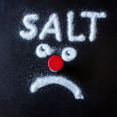 Salt Scattered On Black Surface. Drawn Word- Salt And Sad Face. Concept- Diet, Harm To Health From E poster