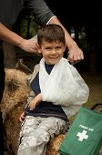 image of sling bag  - First Aid treatment given to a young boy in the forest showing an arm sling and a head injury - JPG