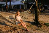 Young American Barefoot Girl Resting On Sand In White Wicker Hammock. poster