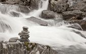 picture of gneiss  - Stacked stones next to a foaming mountain river - JPG