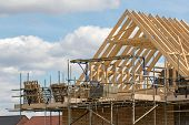 Construction Industry. Timber Framework Of House Roof Trusses With Scaffold On A Building Being Buil poster