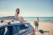 Surfing. Summer Vacation. Extreme Sport. Smiling surfer girl sitting on the car and getting ready fo poster