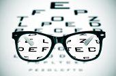 foto of snellen chart  - eyeglasses over a blurry eye chart - JPG