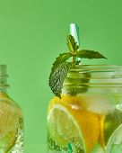 A close-up of a sprig of green mint in focus in a glass jar with cold natural handmade lemonade on g poster