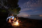Group Of Four Tourists Resting On Lake Shore At Campfire In Front Of Tourist Tent Under Tree, Bearde poster