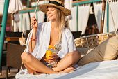 Photo of gorgeous woman 20s in straw hat smiling and holding orange juice while sitting on luxury so poster
