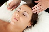 Attractive female reciving face massage with jade roller at acupuncturist poster