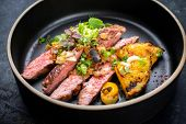 Modern Barbecue dry aged wagyu flank steak with pineapples and chimichurri sauce as top view on a pl poster