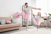 Front View Of Father And Daughter In Tutu Skirts Standing On One Leg poster