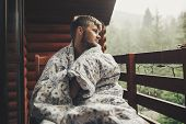 Stylish Bearded Man Relaxing On Wooden Porch Among Forest In Rainy Mountains. Hipster Guy Resting In poster