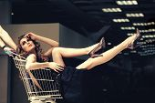 Sensual Woman Sit In Shopping Cart. Girl In Fashionable Dress, Shoes In Trolley In Shop. Fashion, Be poster