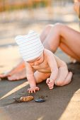 Little Baby Playing With Sand On Beach