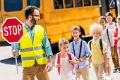 Handsome Traffic Guard Crossing Road With Pupils In Front Of School Bus poster