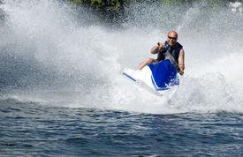 image of waverunner  - action shot of man on seadoo with great waterspray - JPG