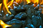 foto of briquette  - Closeup of charcoal in a grill with some ash on briquettes - JPG