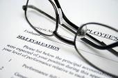 stock photo of self assessment  - Close up of reading glasses  on Employee self evaluation - JPG