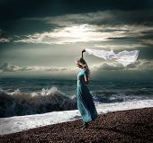 Blonde Woman in Long Dress at Stormy Sea