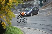 image of bicycle gear  - Man in protective gear with backpack riding bicycle on street - JPG