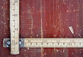 image of meter stick  - Old wooden meter stick on vintage red wooden background  - JPG