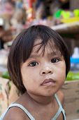 Asian child from impoverished area - natural portrait by a local market in the Philippines.