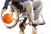 foto of disability  - A disabled basketball player in a tracksuit with a ball - JPG