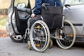 foto of wheelchair  - A disabled driver using a wheelchair entering his car - JPG