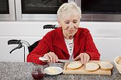 image of disability  - Disabled older woman preparing sandwiches for breakfast - JPG