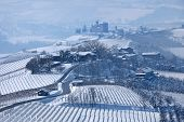 Narrow road through hills covered with snow towards small village in Piedmont, Northern Italy.