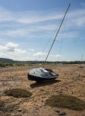 stock photo of anglesey  - A sailing boat stranded by the receding tide in Red Wharf Bay Anglesey Wales - JPG