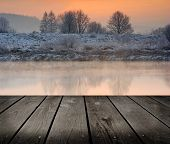 Winter Sunrise Over The River And Empty Wooden Deck Table.