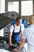 image of auto repair shop  - mechanic talking with female client in auto repair shop - JPG