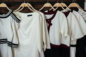 picture of woman red blouse  - Many white blouses on hangers in the dressing room - JPG