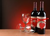 Closeup of a wine bottles decorated for Valentines Day. Two empty wineglasses are next to the bottle