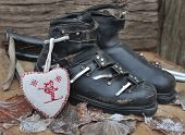 foto of ski boots  - old ski boots in a rustic setting with a heart shaped cushion - JPG