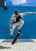stock photo of skateboarding  - Skateboarder jumping on the skateboard in the city - JPG