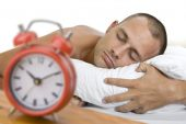pic of unawares  - Man a sleep with big red alarm clock in the foreground - JPG