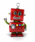 stock photo of cyborg  - Little vintage toy robot waving hello over white background - JPG