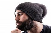 stock photo of beanie hat  - portrait of a thinking man with a beany and a beard maybe a rapper or a gangster - JPG