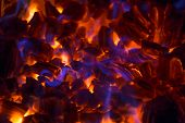 stock photo of ember  - Hot glowing ember in a fireplace with beautiful blue flames - JPG