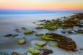 pic of atlantic ocean beach  - The setting sun paints the opposite horizon over the Atlantic Ocean with color along a Florida beach with an outcropping of natural coqunia stone - JPG