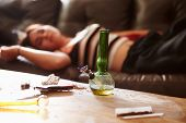 stock photo of crack addiction  - Woman Slumped On Sofa With Drug Paraphernalia In Foreground - JPG