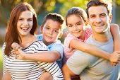 stock photo of hug  - Outdoor Portrait Of Family Having Fun In Park - JPG