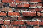 stock photo of mortar-joint  - An uneven weathered old red brick wall with extruded mortar shows texture and depth - JPG