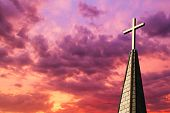 image of calvary  - Colorful sunset sky backs a gleaming golden cross high atop a church steeple